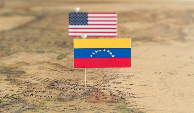 Flaggen der usa und venezuelas auf der weltkarte. konzeptionelles foto, politik und weltordnung