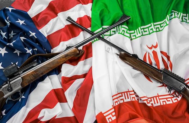 Flaggen des iran und der usa mit gekreuzten waffen