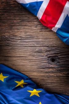 Flaggen des vereinigten königreichs und der europäischen union auf rustikalem eichenbrett uk- und usa-flaggen diagonal zusammen