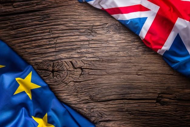Flaggen des vereinigten königreichs und der europäischen union auf rustikalem eichenbrettuk- und usa-flaggen diagonal zusammen