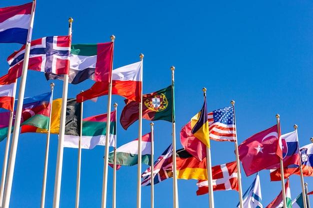Flaggen verschiedener länder flattern im wind gegen einen hellblauen himmel