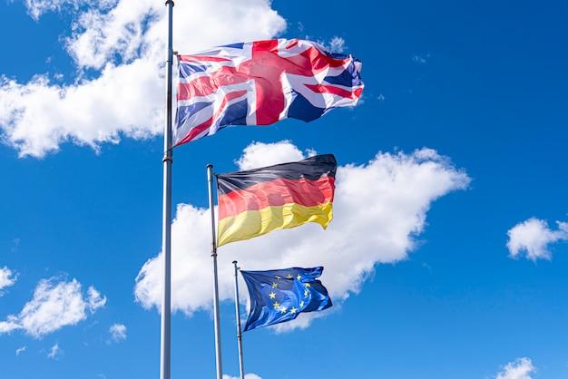 Flaggen von deutschland, großbritannien und der europäischen union in einer straße. eu-, uk- und deutsche flaggen gegen blauen himmel