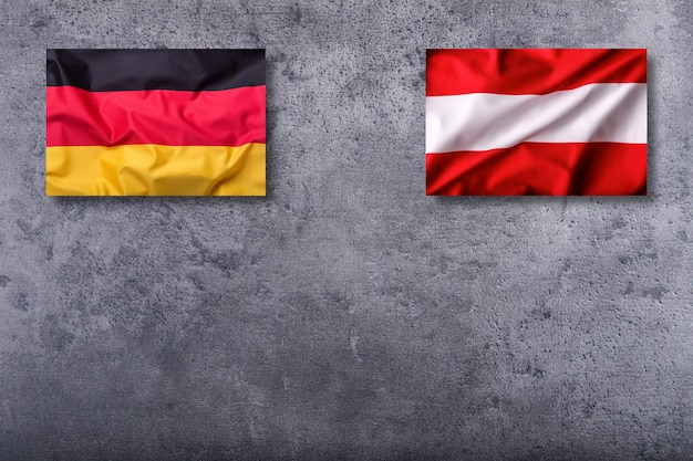 Flaggen von deutschland und österreich auf konkretem hintergrund.