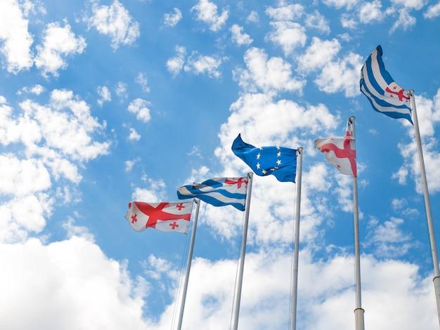 Flaggen von georgien, adjara und der europäischen union auf blauem himmel