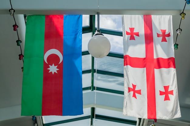 Flaggen von georgien und aserbaidschan hängen an der decke