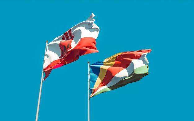 Flaggen von gibraltar und seychellen auf himmelhintergrund