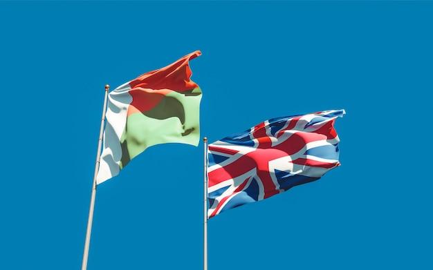 Flaggen von madagaskar und britischen briten auf blauem himmel. 3d-grafik