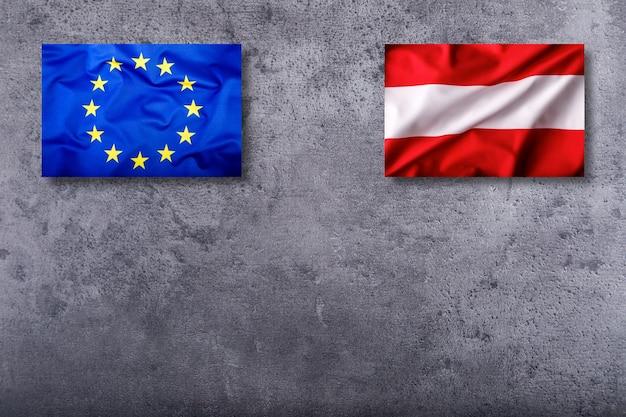 Flaggen von österreich und der europäischen union auf konkretem hintergrund.