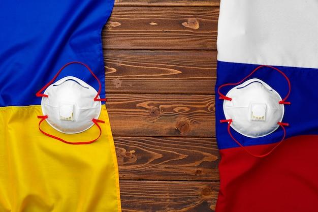 Flaggen von russland und der ukraine auf hölzernem hintergrund mit medizinischen masken
