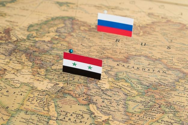 Flaggen von russland und syrien auf der weltkarte. konzeptionelles foto, politik und weltordnung