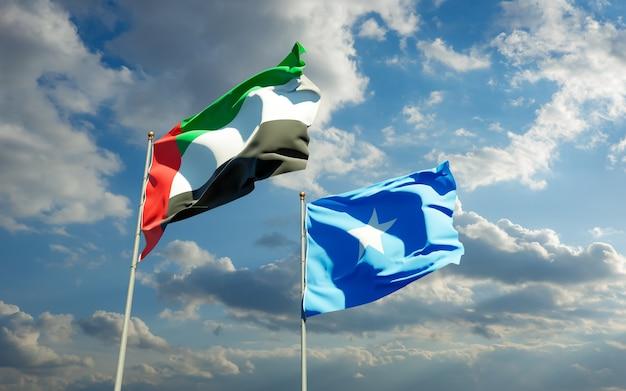Flaggen von somalia und den arabischen emiraten der vae auf blauem himmel. 3d-grafik