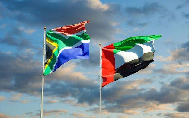 Flaggen von südafrika und den arabischen emiraten der vae auf blauem himmel. 3d-grafik