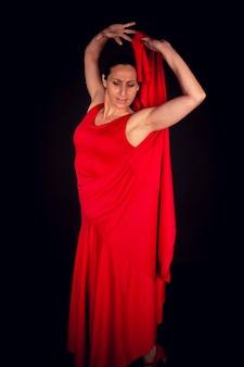 Flamenco-frau, die rotes kleid mit erhobenen händen trägt