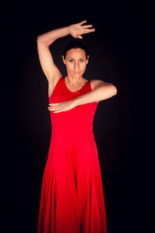 Flamenco-frau, die rotes kleid mit erhobener hand trägt