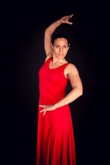 Flamenco-frau, die rotes kleid trägt und sevillianische position ausführt