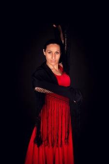 Flamenco-frau, die rotes kleid und schwarzen schal trägt
