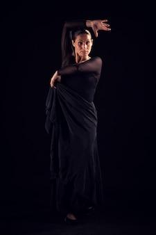 Flamenco-frau mit schwarzem kleid und erhobener hand