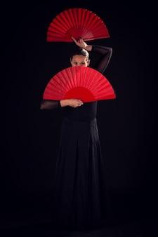 Flamenco-frau mit schwarzem kleid und fächern auf ihrem gesicht
