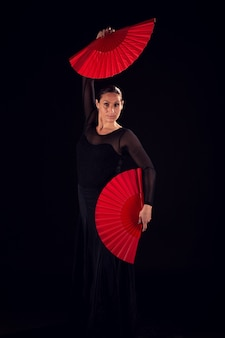 Flamenco-frau mit schwarzem kleid und tanzenden fans