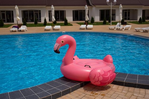 Flamingo-pool-schwimmer im blauen wasserhintergrund, aufblasbarer schwimmschlauch