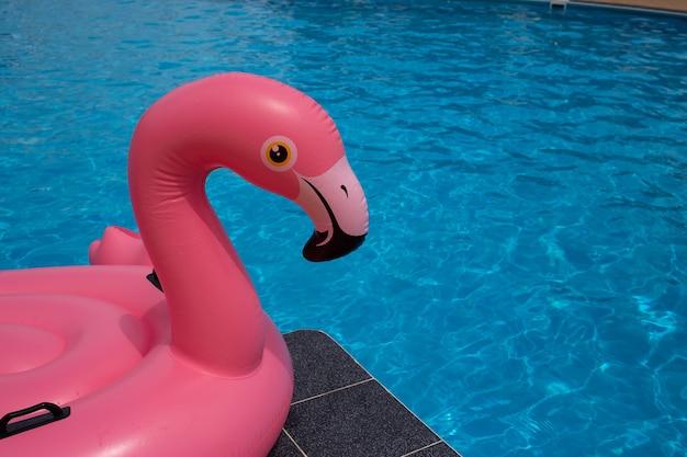 Flamingopool schwimmt im blauen wasserhintergrund des swimmingpools