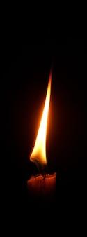 Flamme der kerze, die im dunklen hintergrund brennt