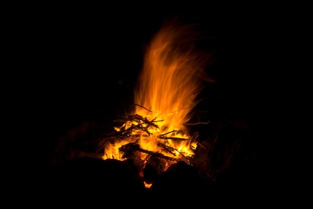 Flamme eines feuers, in dem natürliches reisig brennt, auf schwarzem hintergrund