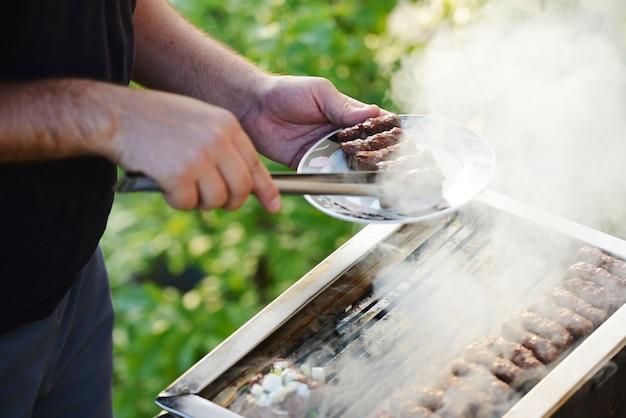 Flammen, die ein steak auf dem bbq grillen