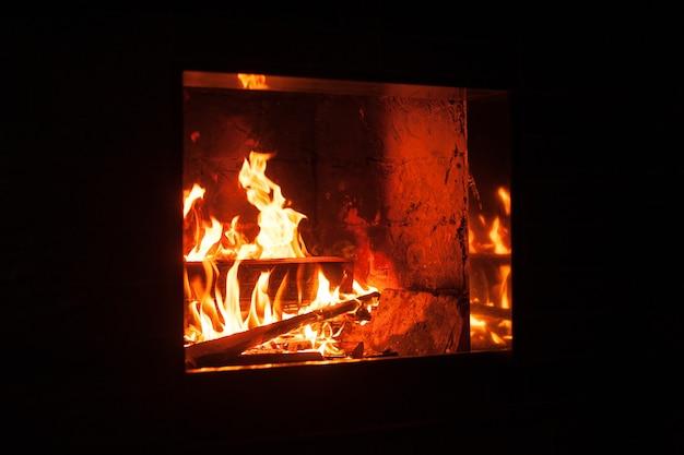Flammen in einem modernen kamin mit glänzendem schieferrahmen.