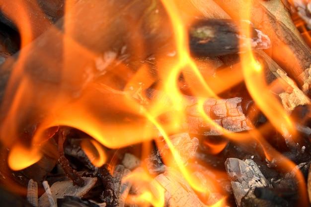 Flammen mit kohlen auf einem feuerhintergrund