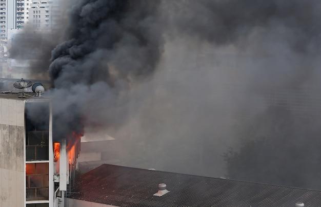 Flammen und rauch steigen vom brennenden gebäude auf