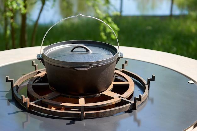Flammende holzkohle in der kesselgrillgrube mit gusseisenrost. runde tisch-kochfläche. bbq hot grill mit edelstahlgitter auf backyard ready grilling cookout essen. grill mit flammen im inneren.