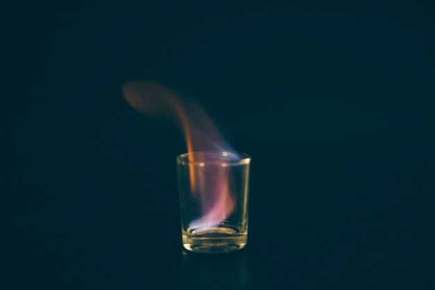 Flammendes tequila-schnapsglas auf schwarzem hintergrund