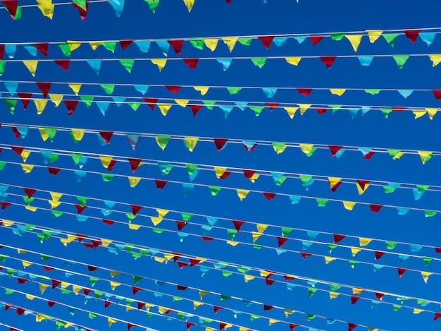 Flammenflaggen bunt auf hintergrund des blauen himmels. feiertagshintergrund.