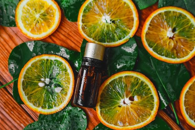 Flasche ätherisches öl aus orangen auf holz