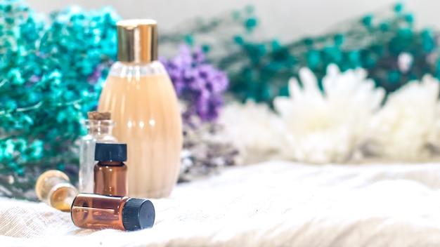 Flasche ätherisches öl. kräutermedizin oder aromatherapie-tropfflasche isoliert auf weißem hintergrund. frische rosmarinblüten und ätherische öle auf dem tisch