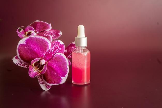 Flasche ätherisches rosenöl, badesalz und phalaenopsis auf weinigem hintergrund. foto in hoher qualität