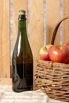 Flasche apfelwein mit frischen äpfeln