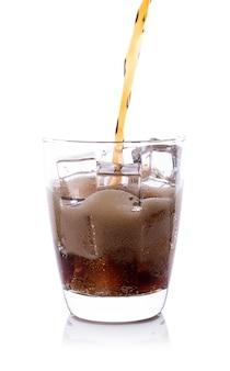Flasche auslaufender cola im getränkeglas mit eiswürfeln
