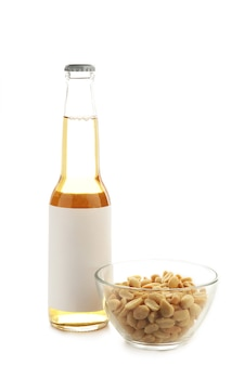 Flasche bier mit erdnüssen auf weißem hintergrund. ansicht von oben