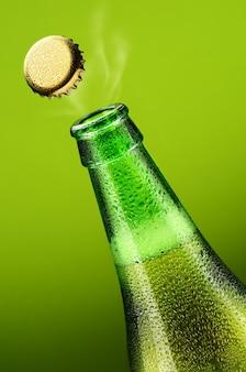 Flasche bier mit öffnungsdeckel auf grün