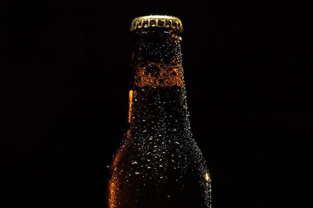 Flasche bier mit wassertropfen nahaufnahme auf einem schwarzen isolierten hintergrund.