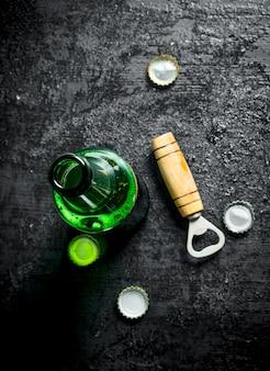 Flasche bier und öffner. auf schwarzem rustikalem tisch