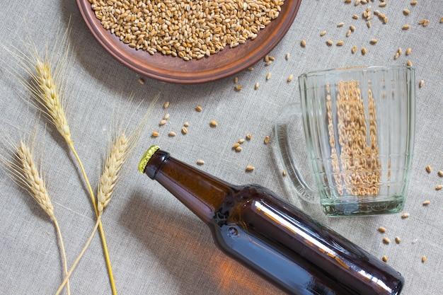Flasche bier, weizen, leerer becher auf sackleinen.