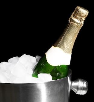 Flasche champagner im eimer mit eis, auf schwarzer oberfläche