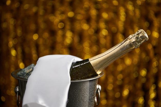 Flasche champagner in einem eimer mit eis auf dem goldenen bokeh