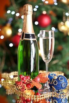 Flasche champagner mit glas und weihnachtskugeln am weihnachtsbaum