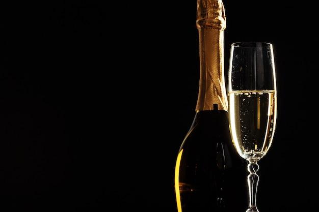 Flasche champagner und gläser über dunkelheit