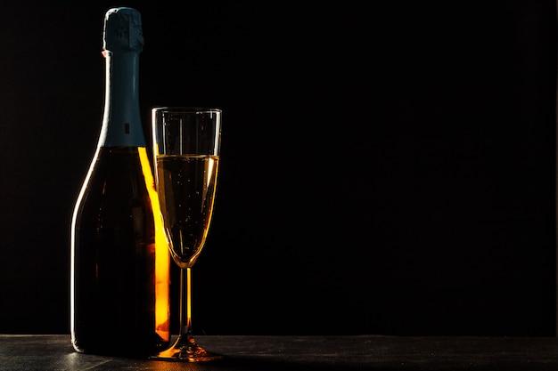 Flasche champagner und gläser über dunklem hintergrund