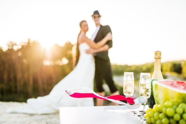 Flasche champagner und zwei gläser vor dem hintergrund verschwommener umarmter braut und bräutigam